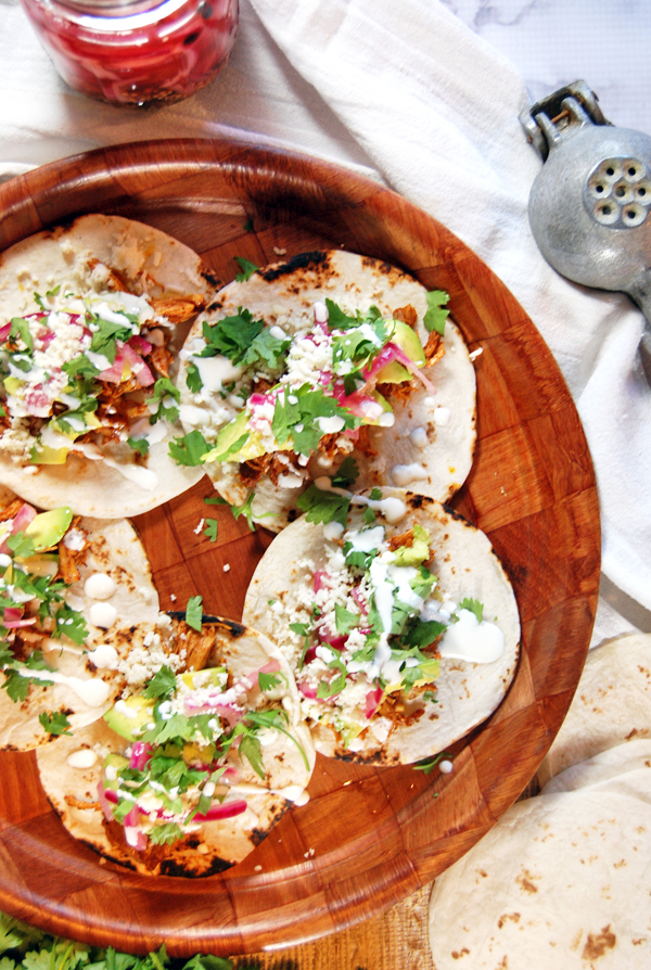 Ancho Achiote Shredded Chicken Tacos with Pickled Red Onions, Avocado, and Crema