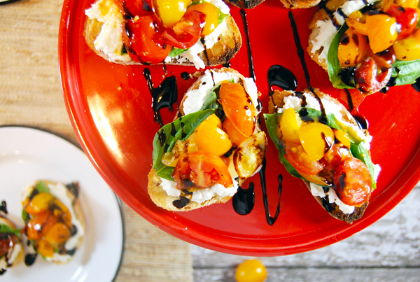 Grilled Cherry Tomato Salad Crostini with Whipped Burrata and Balsamic Glaze: A quick 30 minute crostini! The classic flavor combination of cherry tomatoes, balsamic glaze, whipped burrata, and basil in an easy 2-bite appetizer!