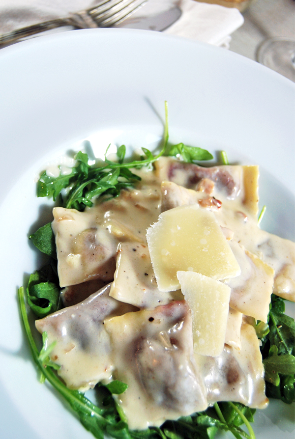 Roasted Beet and Pancetta Agnolotti with Creamy Goat Cheese Sauce and Arugula: A heart agnolotti recipe featuring roasted beet and pancetta with a creamy goat cheese sauce and fresh arugula.