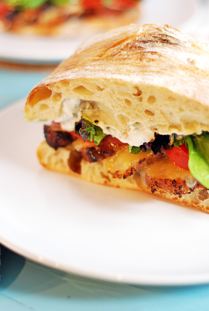 Crispy Pork Belly Sandwich: Tasty pork belly is the star of this sandwich, where it is paired with roasted garlic cilantro aioli, white cheddar cheese, and fresh tomatoes and greens.