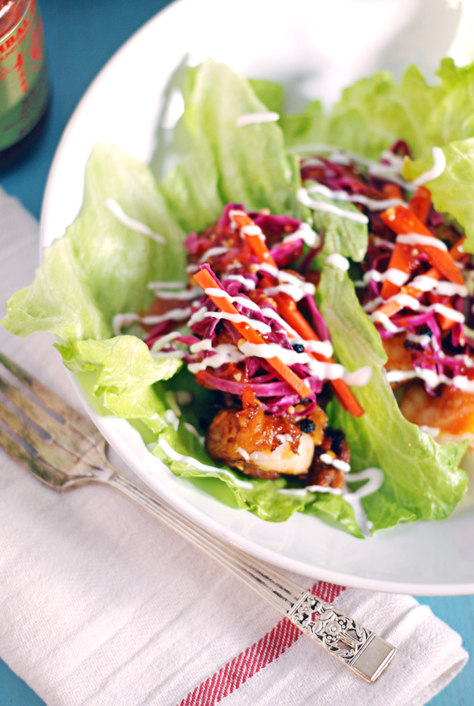 Fried Shrimp Lettuce Wraps with Pickled Vegetables, Chili Sauce, and Crema: A healthy seafood lettuce wrap is paired with beautifully pickled cabbage and carrots, spicy hot chili sauce, and refreshing crema.