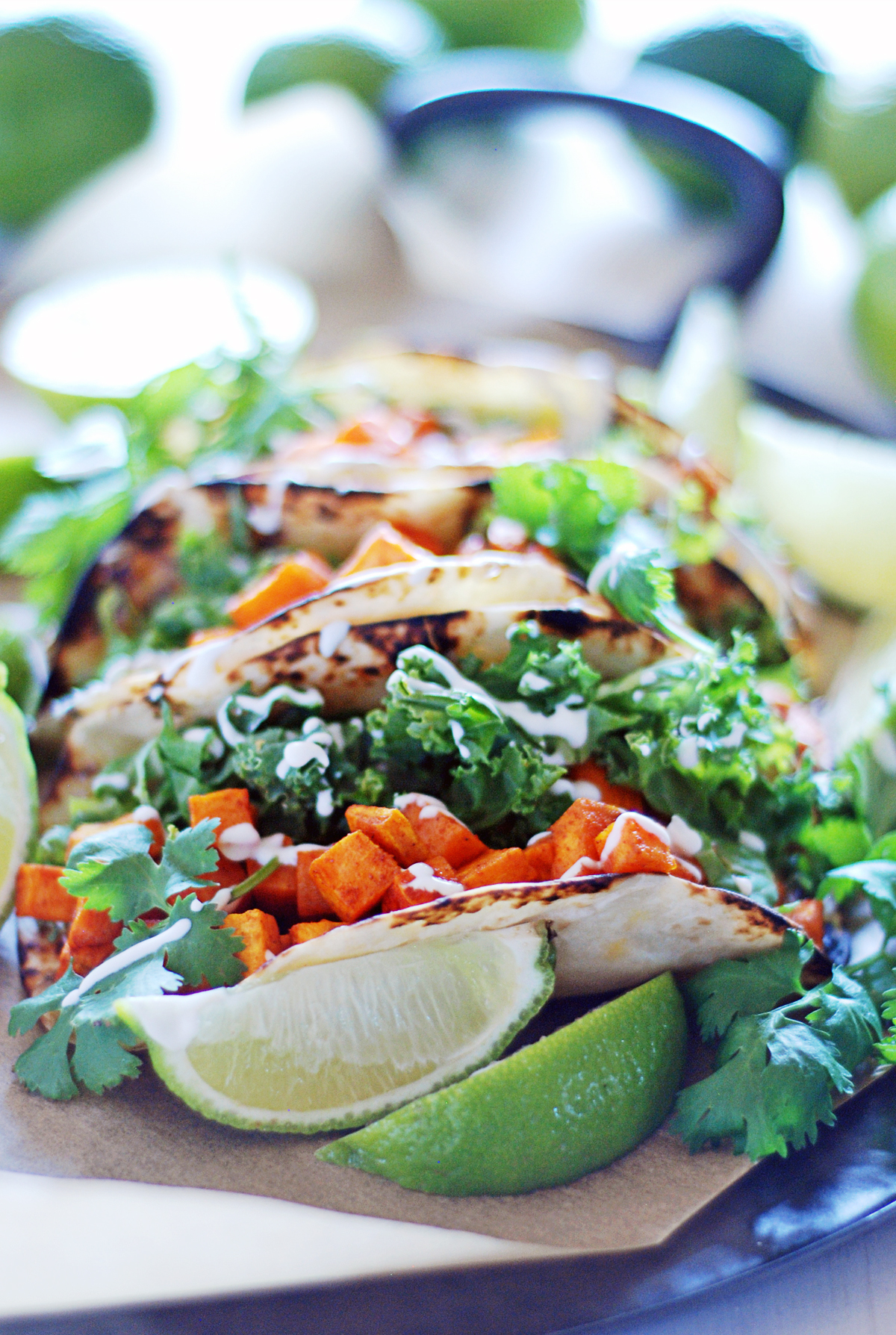 These 10 ingredient roasted sweet potato tacos with cilantro pesto, white cheddar and crema are ready in under 45 minutes!