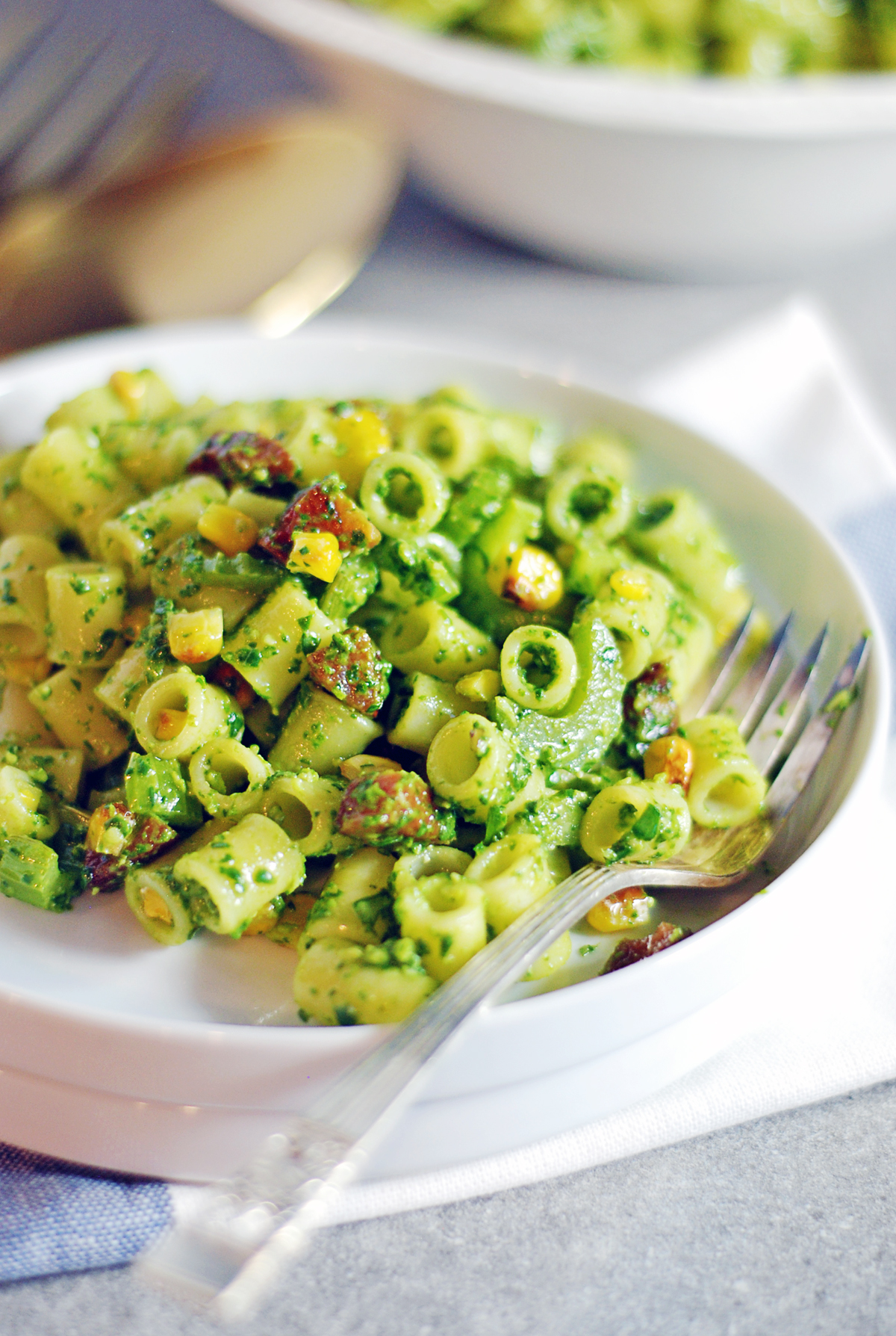 This roasted corn pasta salad features delicious oven-roasted corn and celery with fresh spinach pesto and crispy pancetta.