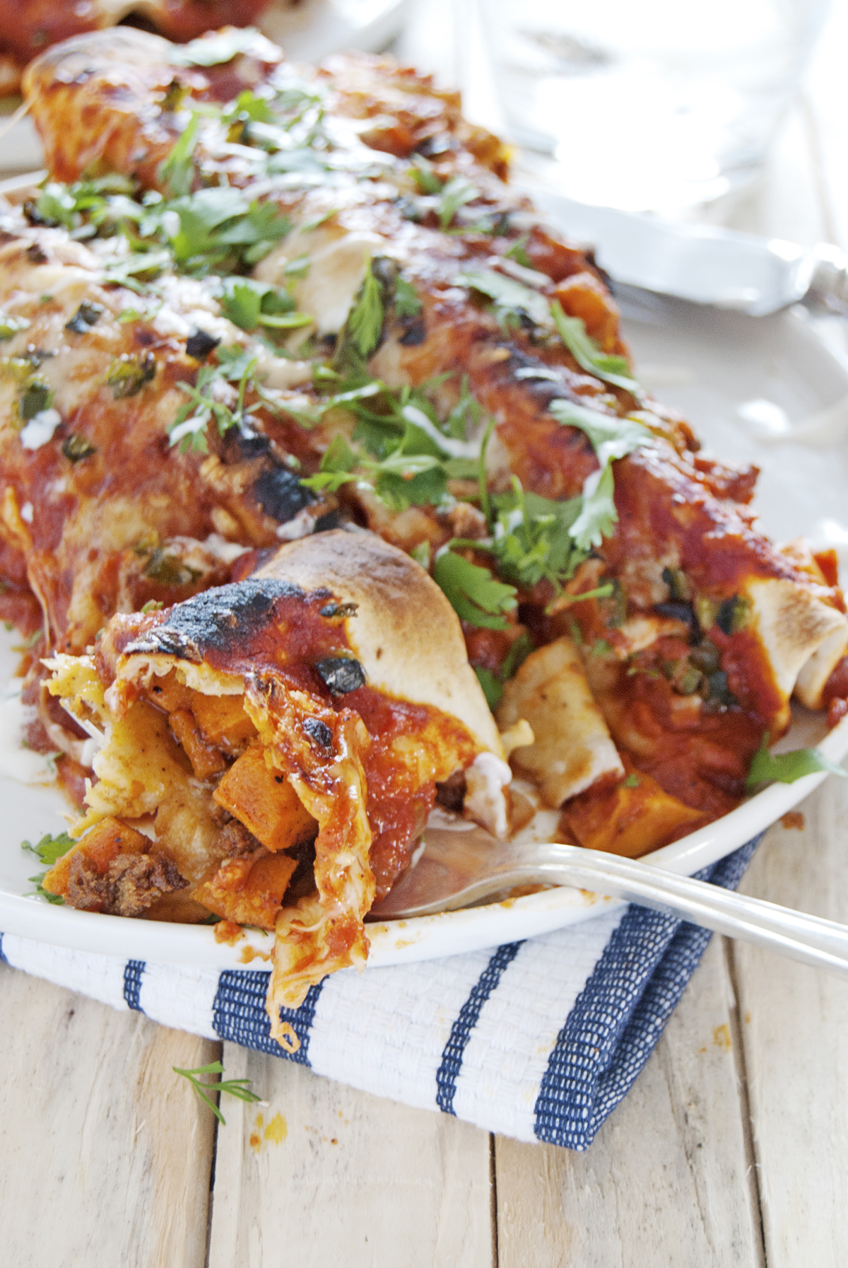 These tasty chorizo and sweet potato enchiladas feature creamy fontina cheese, homemade red enchilada sauce, and roasted poblano peppers.