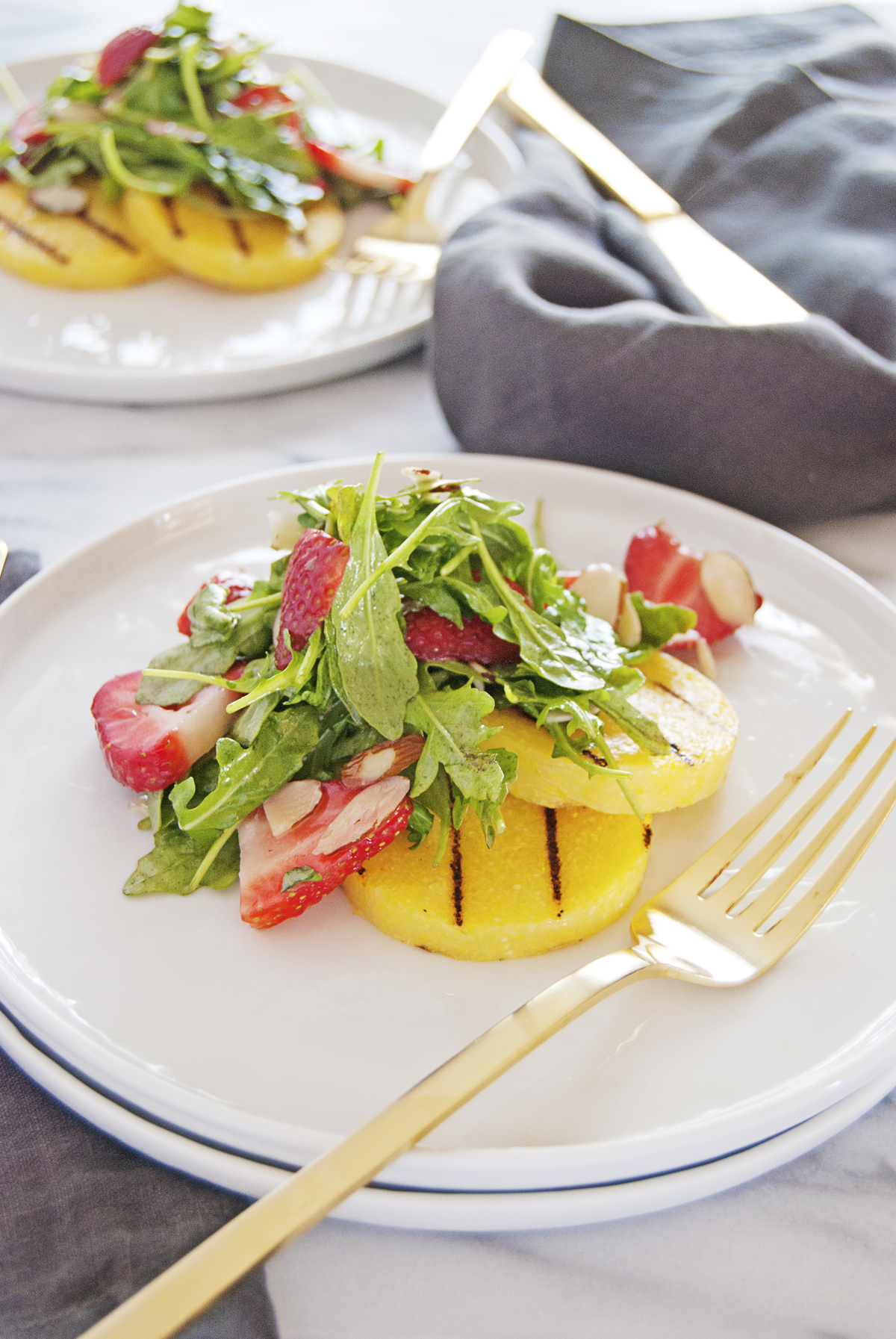 This strawberry arugula salad is so refreshing and features a bright citrus vinaigrette paired with beautifully grilled polenta croutons!