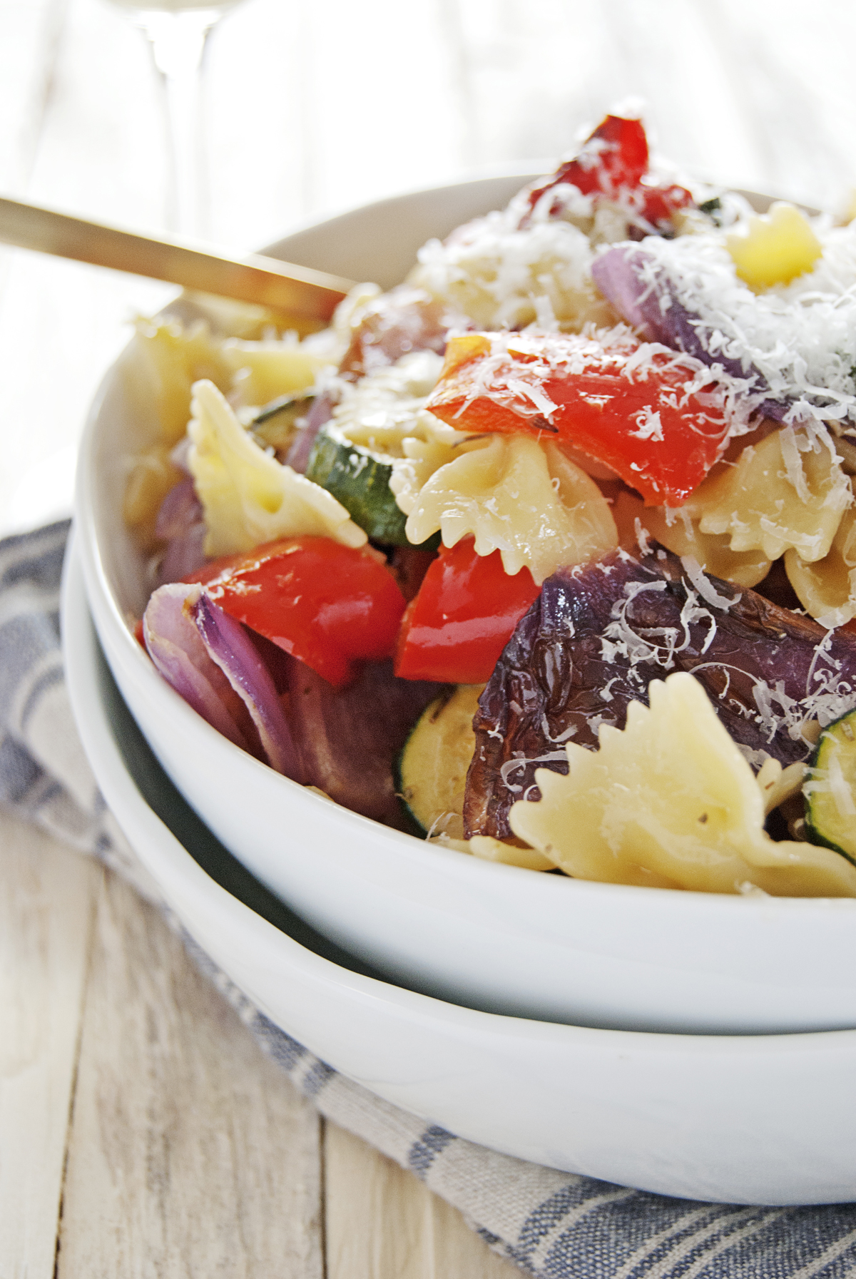 This oven roasted vegetable pasta is a delightfully simple yet tasty vegetarian meal, with oven roasted zucchini, red bell peppers, and red onion.