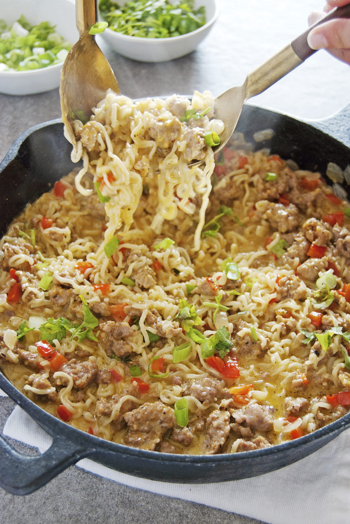 This Mexican-style cheesy ramen dish features spicy pork paired with ramen noodles, cheese, and bell peppers.