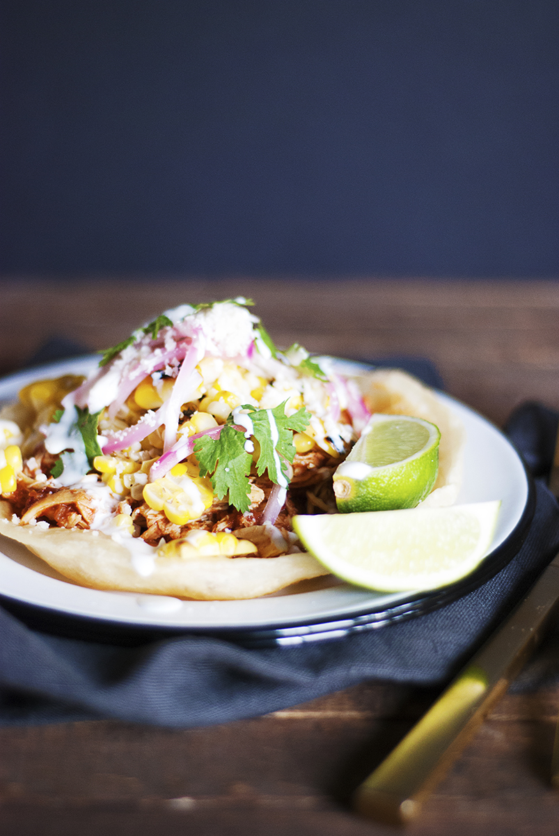 These crispy Mexican chicken tostadas feature a charred corn salsa, quick pickled red onions, fresh cotija, crema and cilantro.