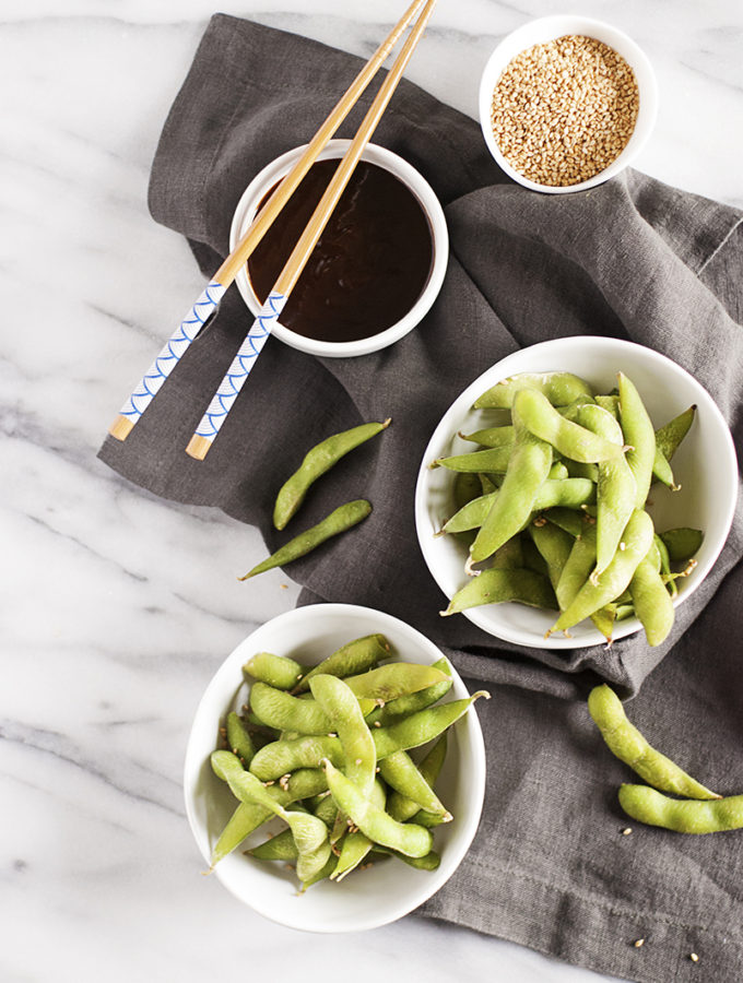 Quick steamed edamame hors d'oeuvres paired with a simple hoisin dipping sauce and toasted sesame seeds.