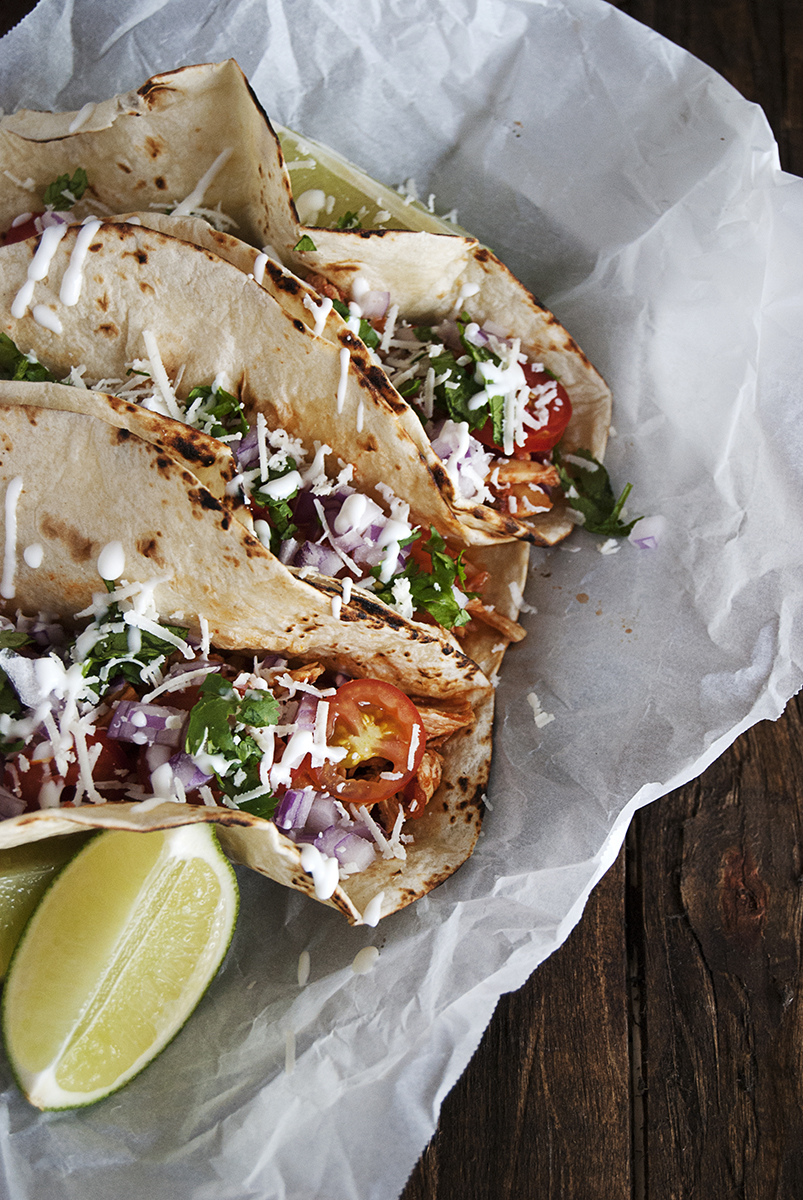 A recipe for slow cooker chicken carnitas tacos featuring tortillas topped with spicy crockpot chicken carnitas, fresh red onion, cherry tomato slices, cotija cheese and fresh crema.