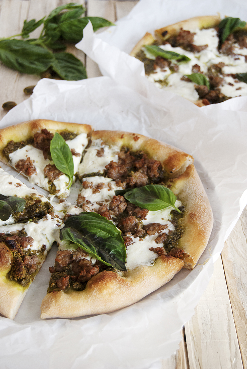 Pistachio pesto pizza, featuring homemade pistachio pesto with crumbled sausage, creamy burrata, and fresh basil.