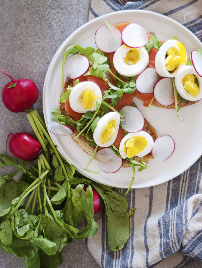 The perfect lunch: egg and cured salmon sandwiches featuring soft boiled eggs, cured salmon, fresh radishes and arugula, and a mustard sauce.