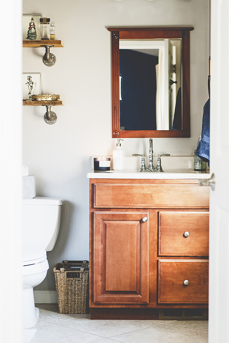 A boring master bath gets a mini-remodel into a gorgeous French country bathroom, with a navy, gray and white color palette and DIY pipe shelving.