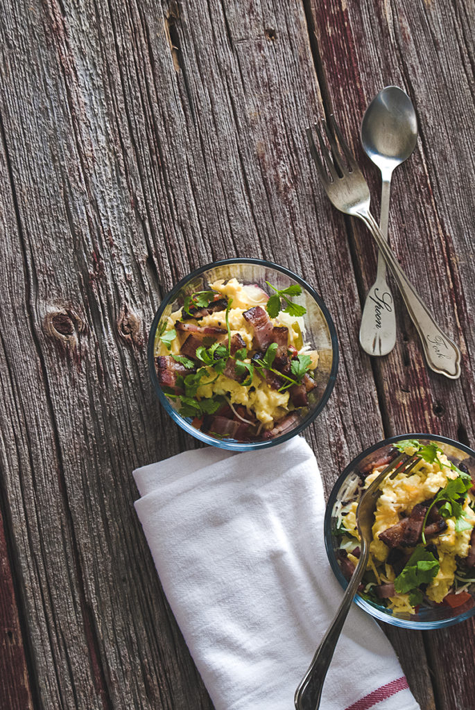These Mexican egg scrambled egg breakfast bowls are easy to prep in advance, and are packed full of goodies, like bacon, potatoes, sautéed peppers and onions, Mexican cheese and cilantro!