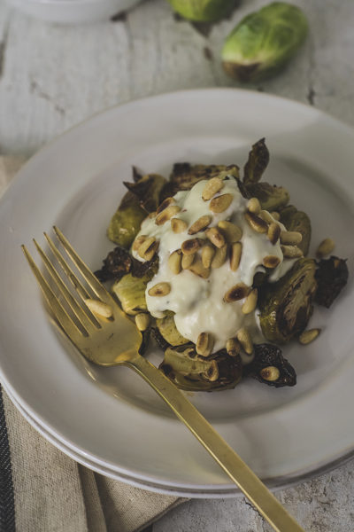 These roasted brussels sprouts with cream sauce will be your new favorite side! They feature a garlic cream sauce, balsamic glaze, and crunchy pine nuts.